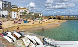 View of the harbour at St Ives, Cornwall. Restaurants and shops can be seen on the promenade and people can be seen on the beach and the promenade.