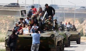 Syrians holding up portraits of President Bashar al-Assad ride on an army personnel carrier in May 2011.
