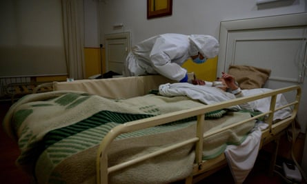 A doctor attends to an elderly woman at a care home near Madrid.