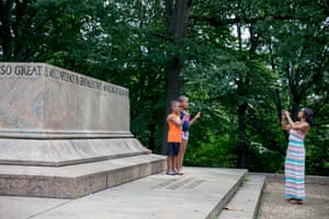 """A family takes photos at the Robert E. Lee and Thomas J. """"Stonewall"""" Jackson monument base in Wyman Park Dell in Baltimore, Maryland, after it was removed by the city on August 16, 2017. Confederate statues were removed overnight in Baltimore, Maryland, as a campaign to erase symbols of the pro-slavery Civil War South gathers momentum across the United States. The removal of the Baltimore monuments came four days after clashes in Charlottesville, Virginia that stemmed from a rally called by white supremacists to protest plans to remove a statue of Lee from a public park."""