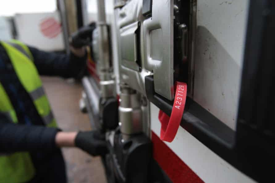 A red seal secures a container door as final preparation for departure.