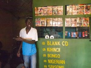 A DVD librarian offers a seat, in Kibera, Kenya.
