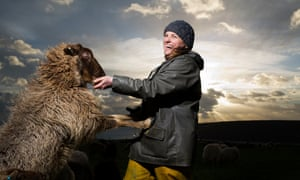 Sheep farmer Rebecca Hosking, photographed with one of her flock on Village Farm in Devon.