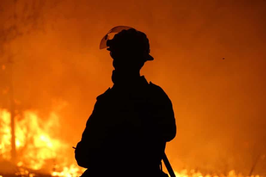 A firefighter defends a property near Potato Point on NSW South Coast on Thursday 23 January 2020.
