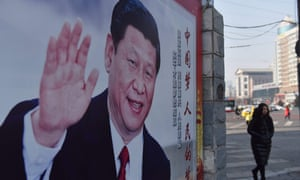 A woman walks past a poster of Xi Jinping beside a street in Beijing.