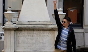 A visitor poses at Alexander Hamilton's gravesite in the yard of Trinity church in lower Manhattan.