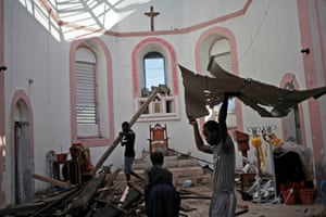 People clear debris from a church a after Hurricane Matthew swept through the town of Les Anglais in Haiti
