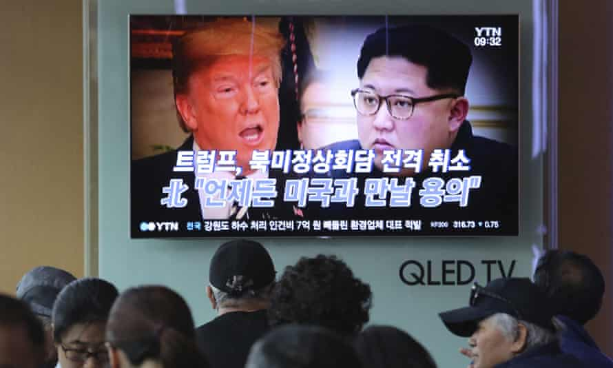South Koreans watch a TV in Seoul showing Donald Trump and Kim Jong-un.