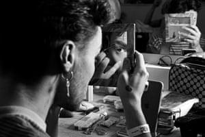 Harvey Rose adjusts his makeup before performing.