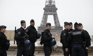 The Eiffel Tower is seen in the background as French gendarmes, part of Operation Sentinelle, patrol the streets
