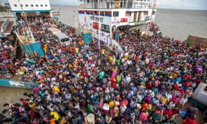 Dhaka bound people disembark from a ferry in Sreenagar on July 31, 2021 to resume and return to their work areas after the Bangladesh government relaxed the lockdown norms for all export oriented factories which were earlier imposed to curb the spread of Covid-19 coronavirus.