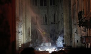 Smoke rises around the altar in front of the cross inside the cathedral
