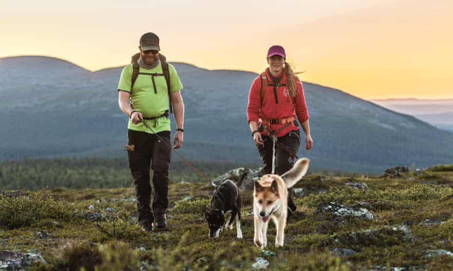 Couple walking huskies at Harriniva Hotel