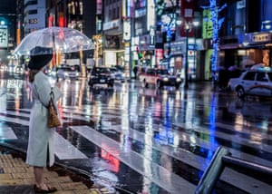 A woman holding an umbrella in a rainstorm stands at Shibuya crossing, at night, in Tokyo, Japan.  By Katy Bridgestock:  I was in Tokyo with a friend in early January and the heavens opened and the streets around Shibuya were suddenly drenched in even more colour and movement. I was taking photos of vehicles while my friend was holding the umbrella. In a break from pictures of cars, I noticed this lady at the crossing. I'm pleased with the futuristic feel of the image.