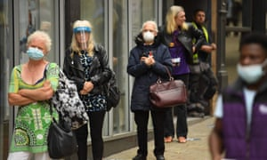 People wear PPE facemasks and visors as they queue to enter a bank in Leeds, UK.