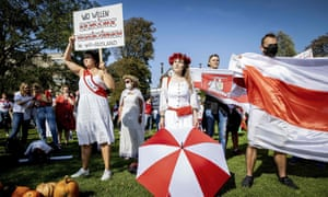People hold a former white-red-white flag of Belarus as protesters gather in front of the Belarusian embassy in The Hague, the Netherlands.