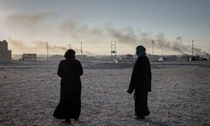 Two women walk through eastern Mosul