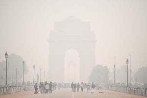 People walk along Rajpath near India Gate under heavy smog conditions.
