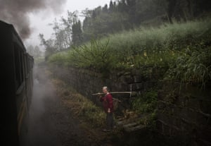 A villager walks on the rail tracks near the former mining town of Bagou