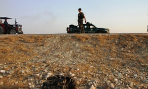 An Afghan security force member inspects at the site of a motor bombing in Behsoud district of Nangarhar province, Afghanistan, in August.