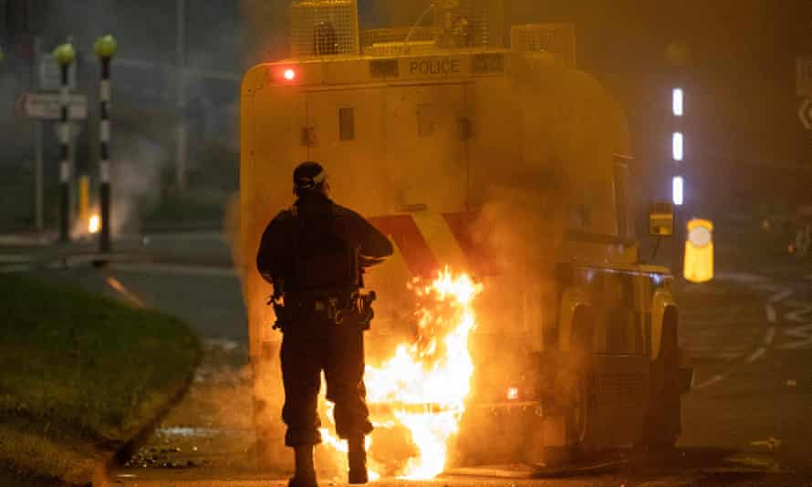 An officer walks behind a police vehicle with flames leaping up the rear amid violence in Newtownabbey, north of Belfast