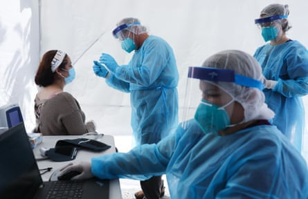 Healthcare workers prepare to test a woman at a mobile clinic in Los Angeles, California, on 15 July.