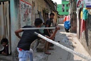 A plainclothes policeman wields his baton against a man as a punishment for breaking the lockdown rules in Kolkata