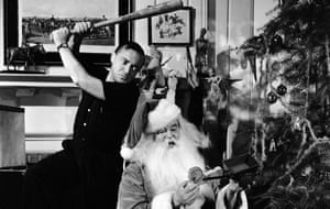 Black and white photograph of Peter Lorre holding a baseball bat over Sydney Greenstreet dressed as Father Christmas