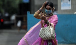 A transgender woman checks her make-up on the road in Mumbai, India, in July