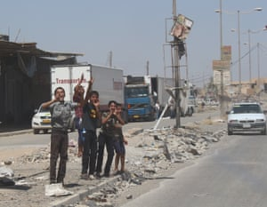 Kids cheer on the passing cars in new Mosul on 11 July.