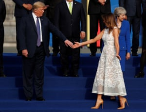 President Trump and the US first lady get ready for a photo at the Park of the Cinquantenaire