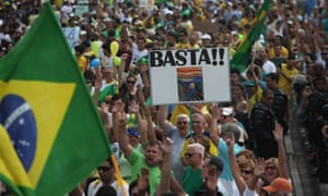 Demonstrators hold up a sign reading 'enough' at a rally in Rio de Janeiro against the Petrobras corruption scandal.