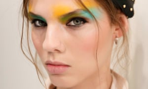 Close-up of a model's face with bright green and yellow eyeshadow and wisps of hair around her face