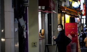 A woman wearing a face mask waits for her food at Dongseong-ro shopping street in central Daegu, South Korea.