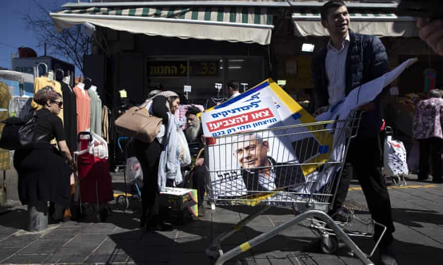 A Netanyahu supporter carries his election posters after a campaign rally at a market in Jerusalem.