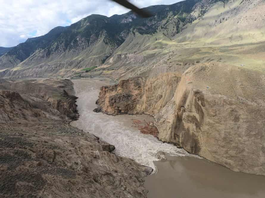 An aerial view of a dampened rock face over the Fraser River during a morning helicopter sluicing operation, near Big Bar, British Columbia
