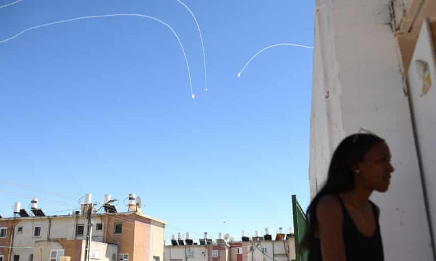 Iron Dome explosions are seen in sky above an Israeli woman as she is getting into a into a public bomb shelter,