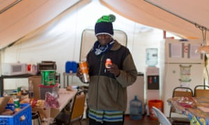 A resident named Adrian in the communal kitchen tent at Othello Village