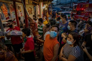 """Filipinos wearing facemasks to protect against Covid-19 queue to buy roasted pigs known locally as """"lechon"""", a dish popularly eaten during celebrations, as they mark New Year's Eve on 31 December, 2020 in Quezon city, Metro Manila, Philippines."""