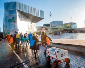 Children carry 6000 books from the city's old library to the new Deichman library in Oslo, Norway