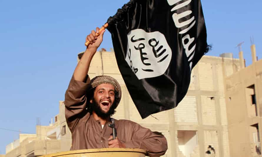 Escalating repression … an Isis fighter waves a flag during a military parade in Raqqa in 2014.