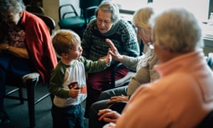 A young boy from the nursery of 'the Mount' gets to know some of the elderly residents.