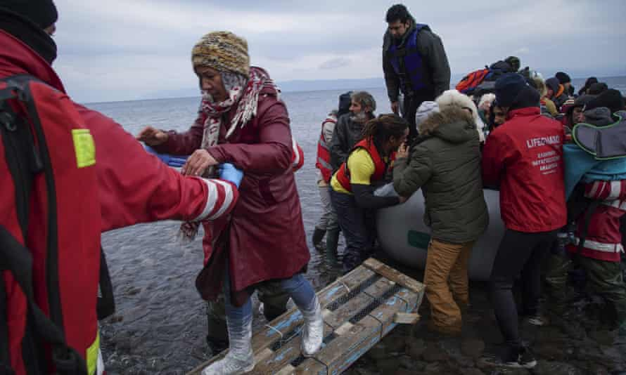 Members of the Greek Red Cross help migrants and refugees to disembark from an inflatable boat in Lesbos.