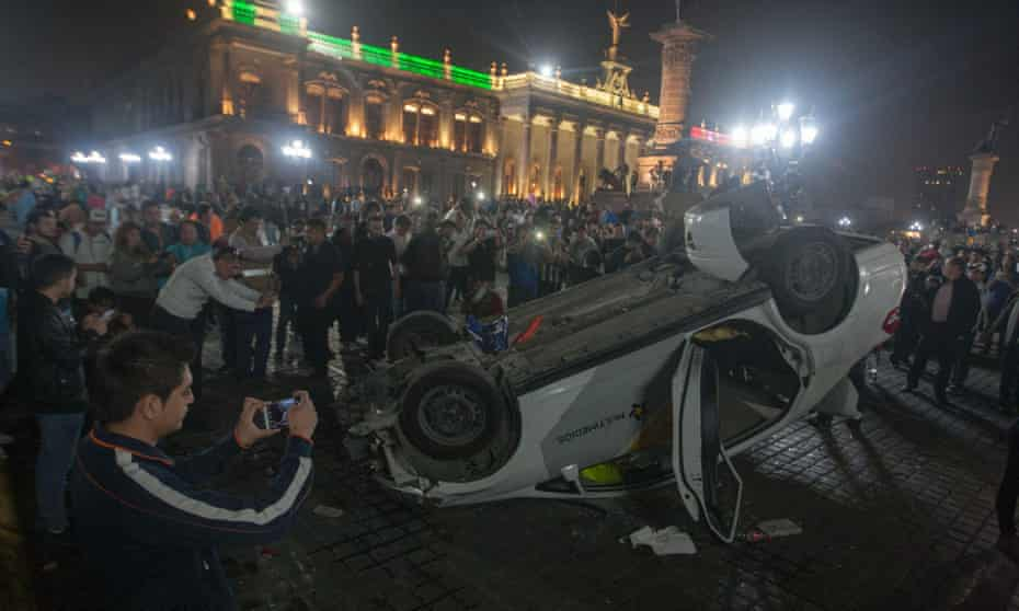 A car is overturned outside the Palacio de Gobierno in Monterrey Nuevo Leon on Thursday night after Mexico's government imposed a 20% rise in the price of gasoline.
