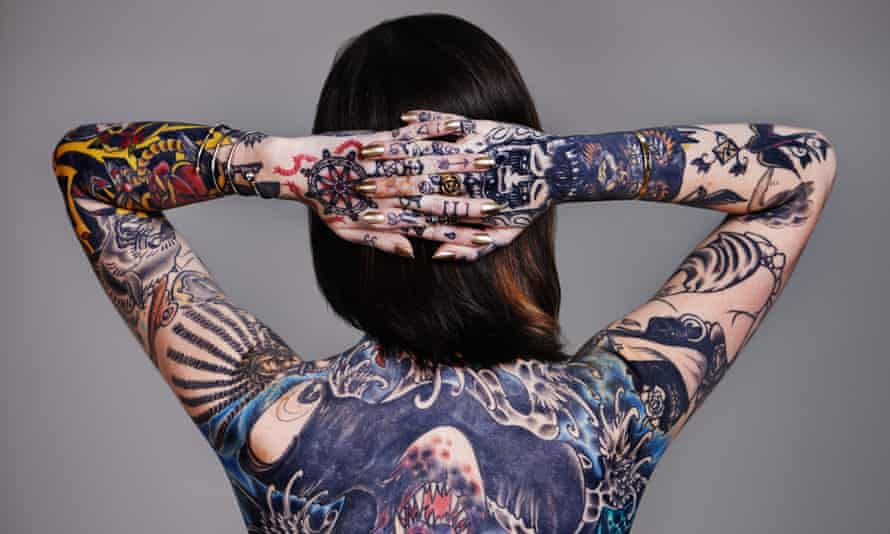 A heavily tattooed young woman