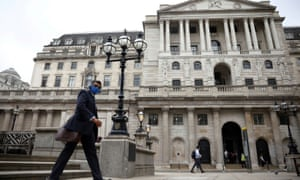 A person walks past the Bank of England in the City of London financial district.