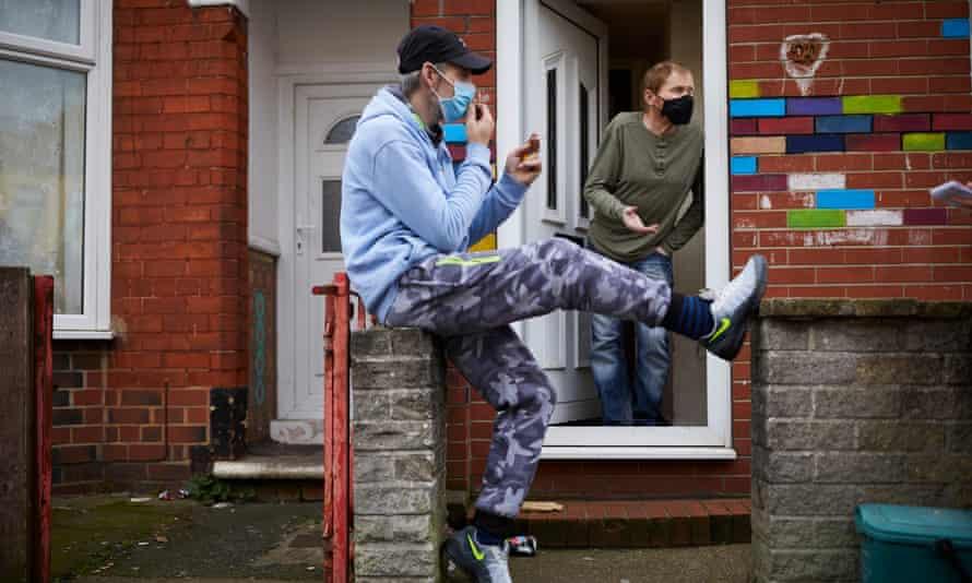 Samy Hassan (sitting) and Gavin Storey (black mask) talking on the doorstep in Gipsyville
