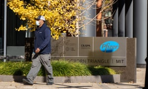 A man walks past a sign outside of a facility occupied by Pfizer laboratory on Port Street in Cambridge, 10 November 2020.