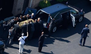 The casket bearing the remains of Muhammad Ali is loaded into a hearse before the funeral procession