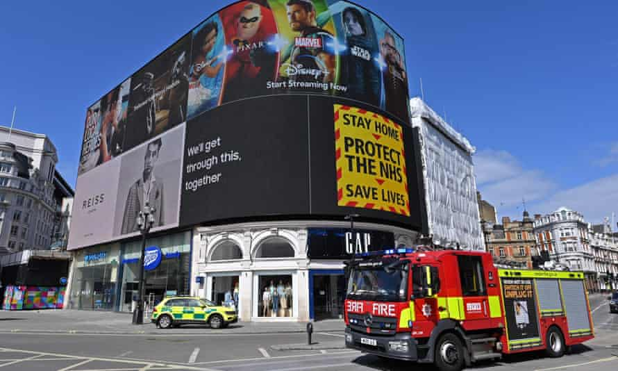 A government notice advising people to 'stay home, protect the NHS, save lives' is displayed on a large screen at Piccadilly Circus in central London